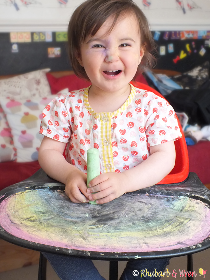 baby playing with chalk in highchair