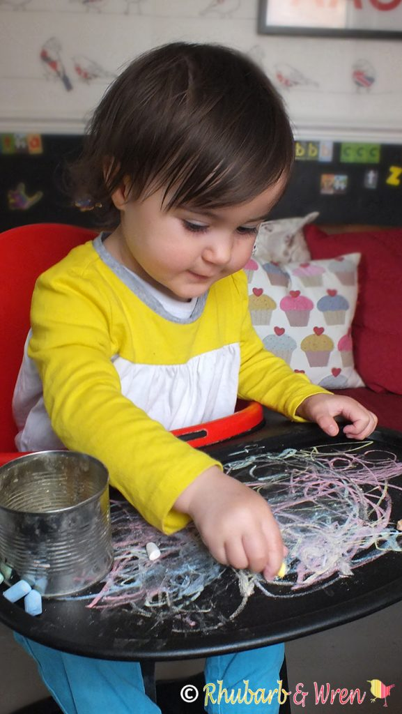 baby drawing with chalk on highchair table