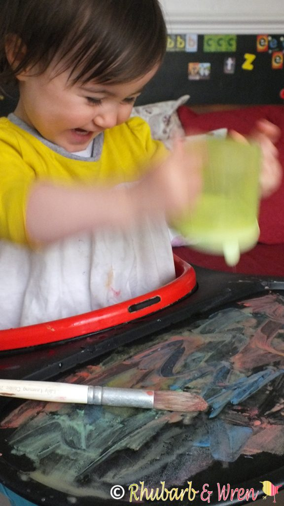 baby pouring water onto highchair table