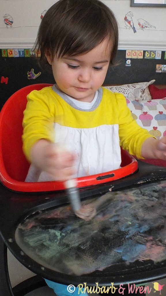 baby drawing with paintbrush, water and chalk