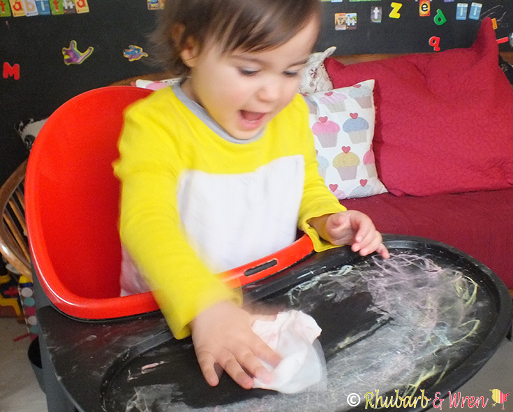 baby cleaning highchair table with wet cloth