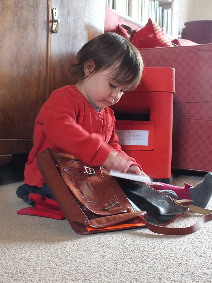 toddler posting letters in pretend play postbox
