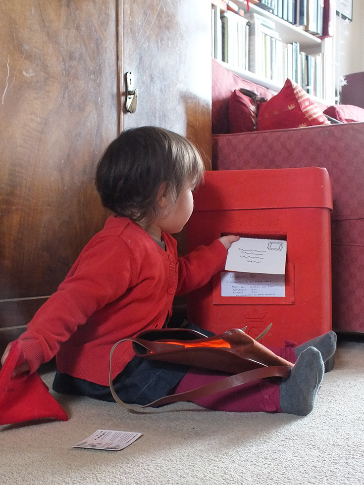 child posting letters in play postbox