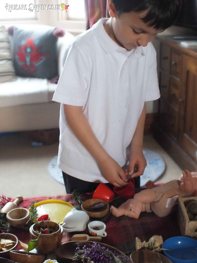 Boy making pretend tea with doll