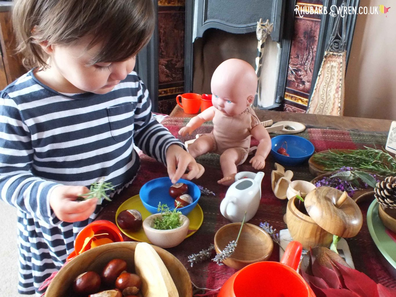 Toddler making doll's tea party with leaves, herbs and flowers