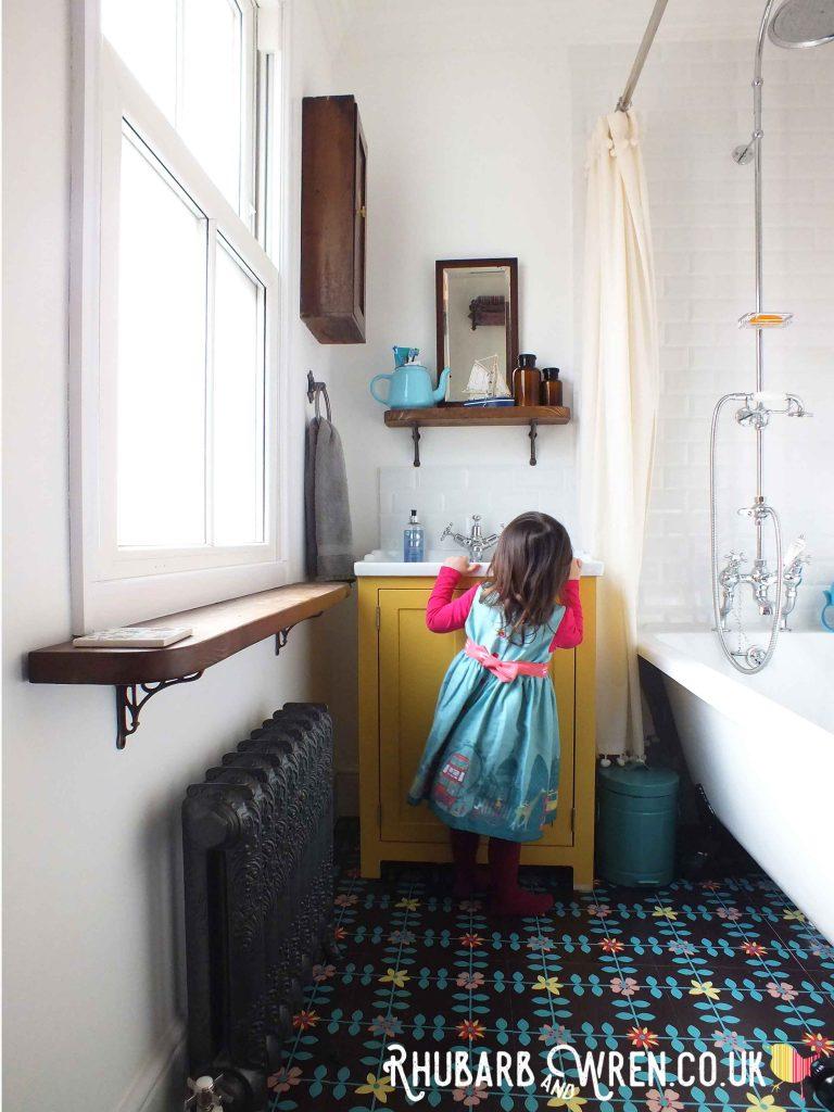 little girl in colourful bathroom