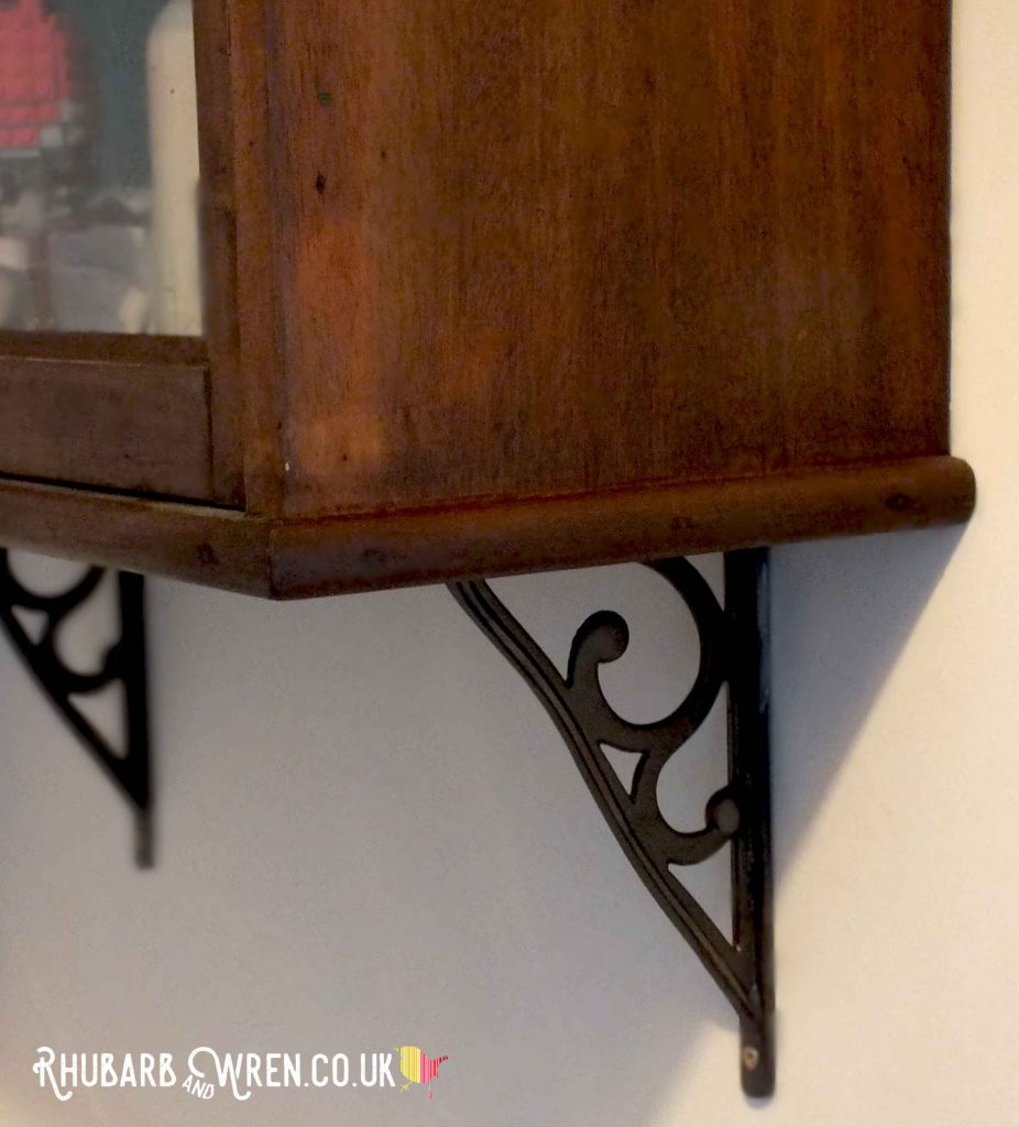 Cast-iron brackets supporting a wall cabinet