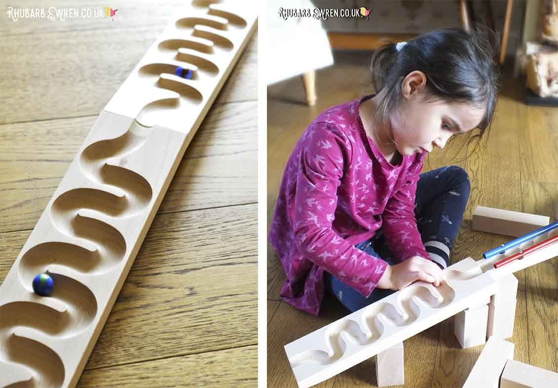 Child playing with HABA wooden marble run section 'winding track'