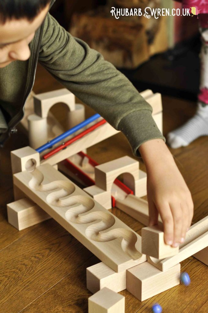 Boy playing with a wooden marble run from toy company HABA