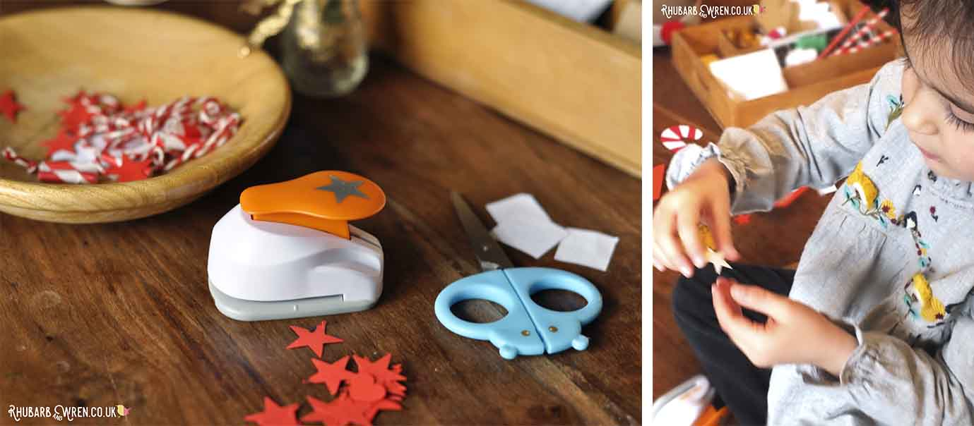 child cutting out paper stars with craft punch