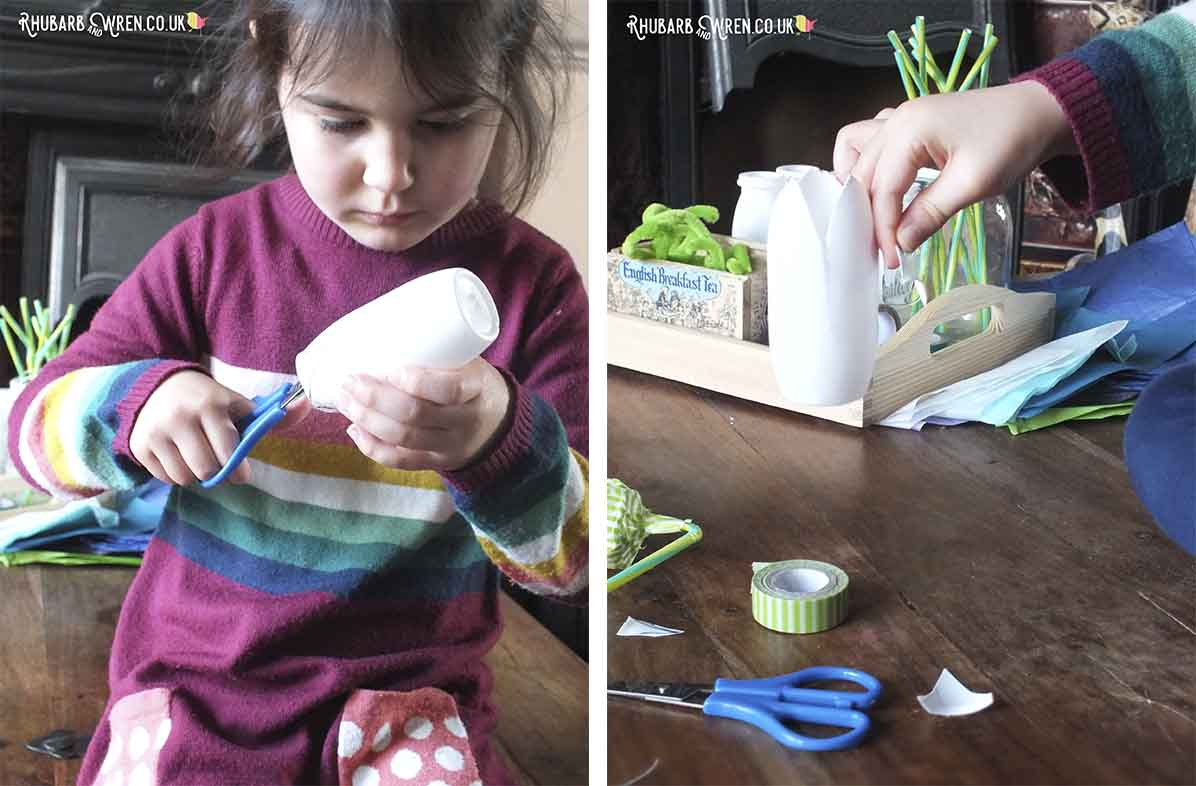 Child cutting out petal shapes in plastic bottle