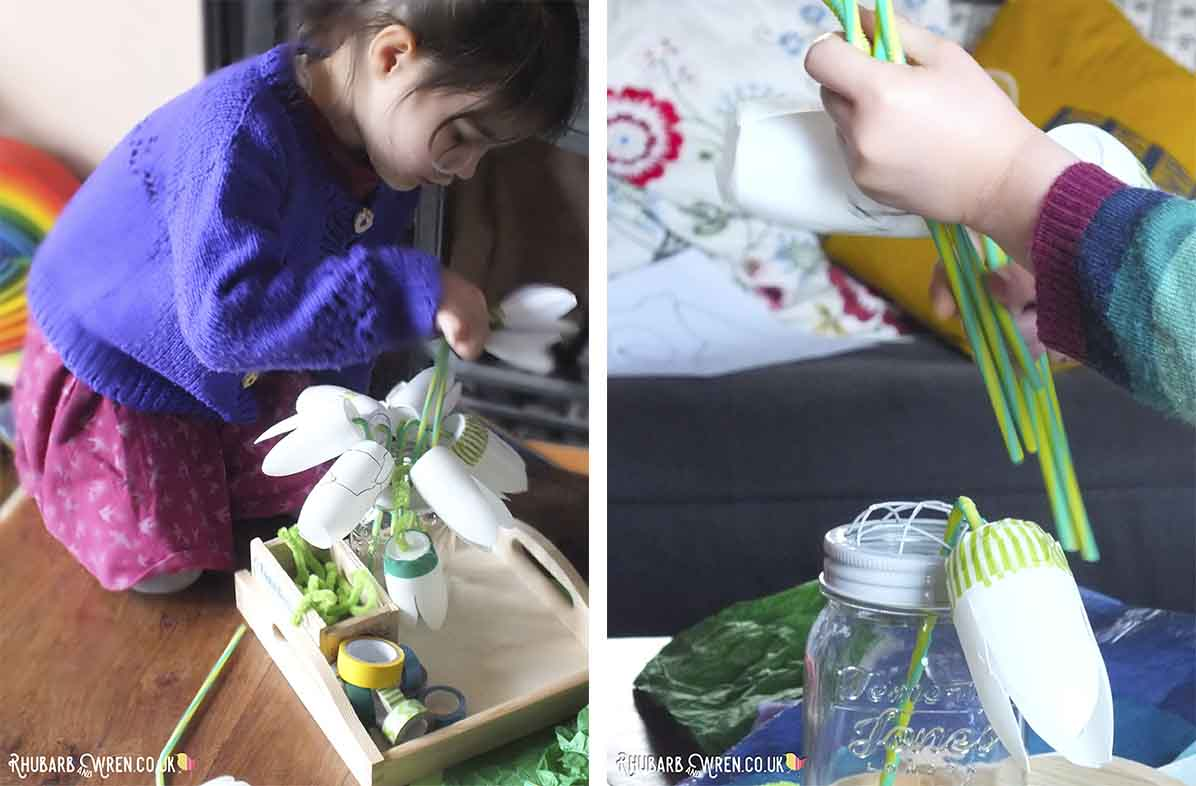 Child arranging paper flowers in a vase