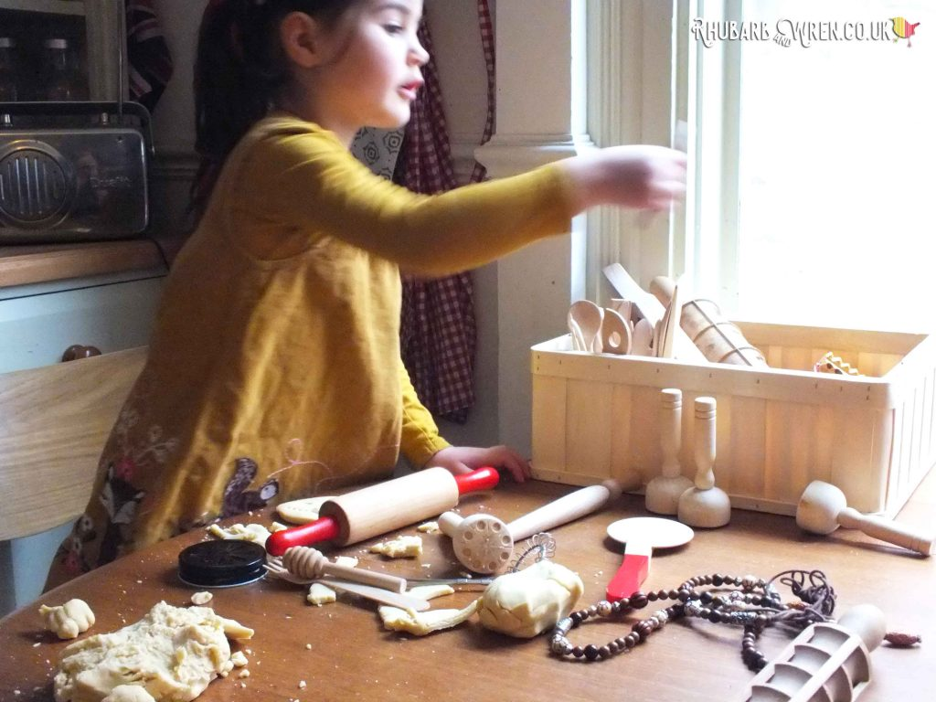 Child playing with play dough tools and accessories made from natural materials.