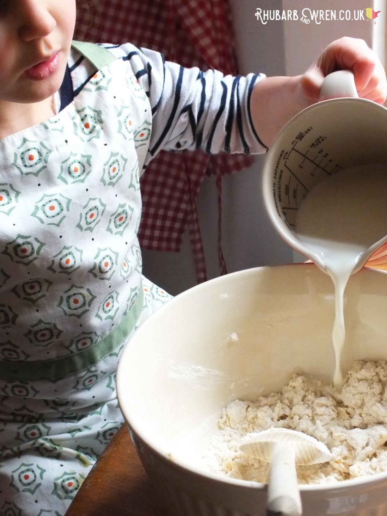 Child pouring milk into mixing bowl.