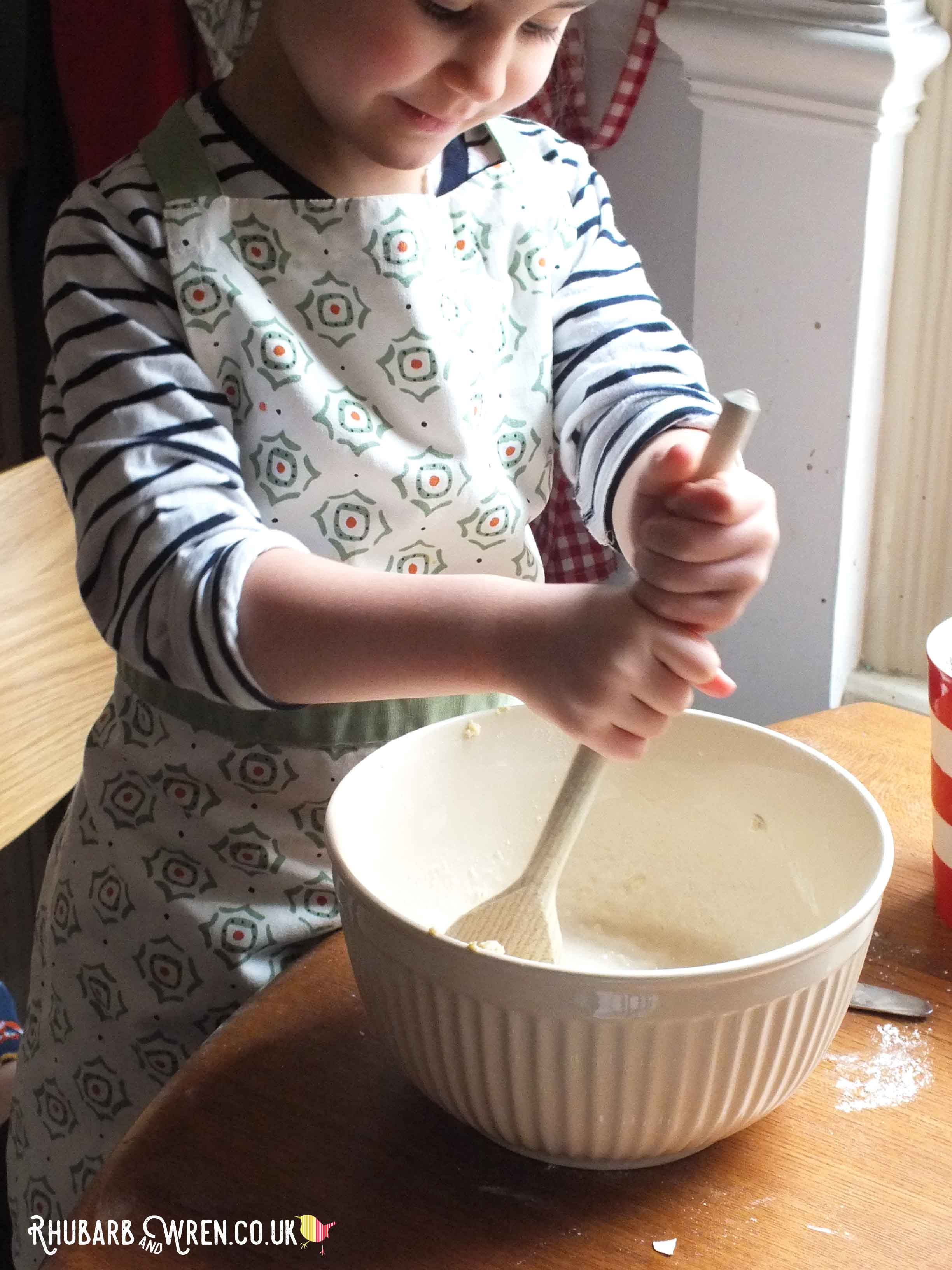 child stirring a bowl of pancake batter