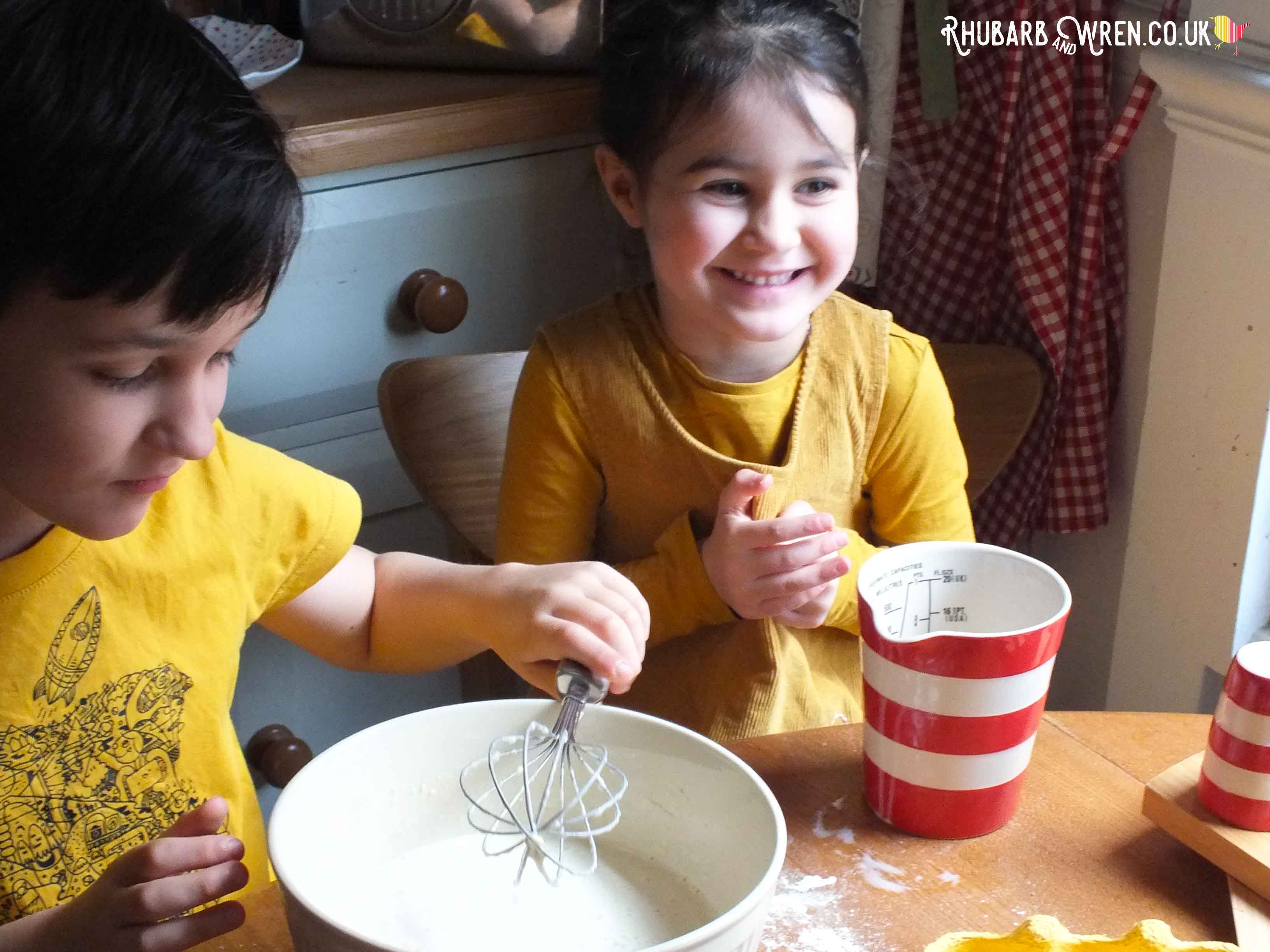 Children smiling as they finish mixing up pancake batter.