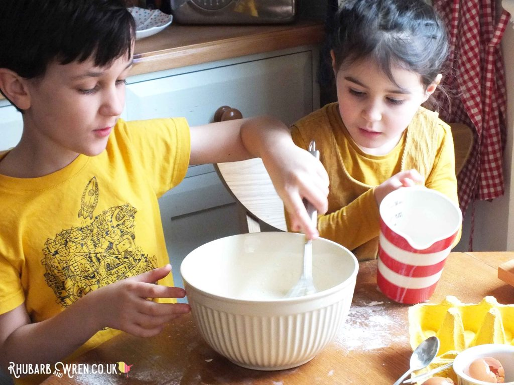 Children using a whisk to mix pancake batter.