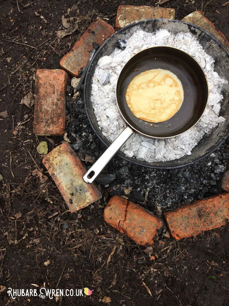 Cooking pancakes on a campfire.