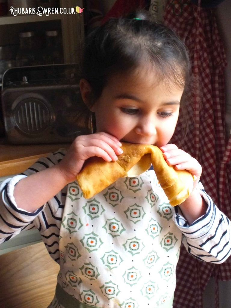 Child biting into yummy rolled-up pancake.
