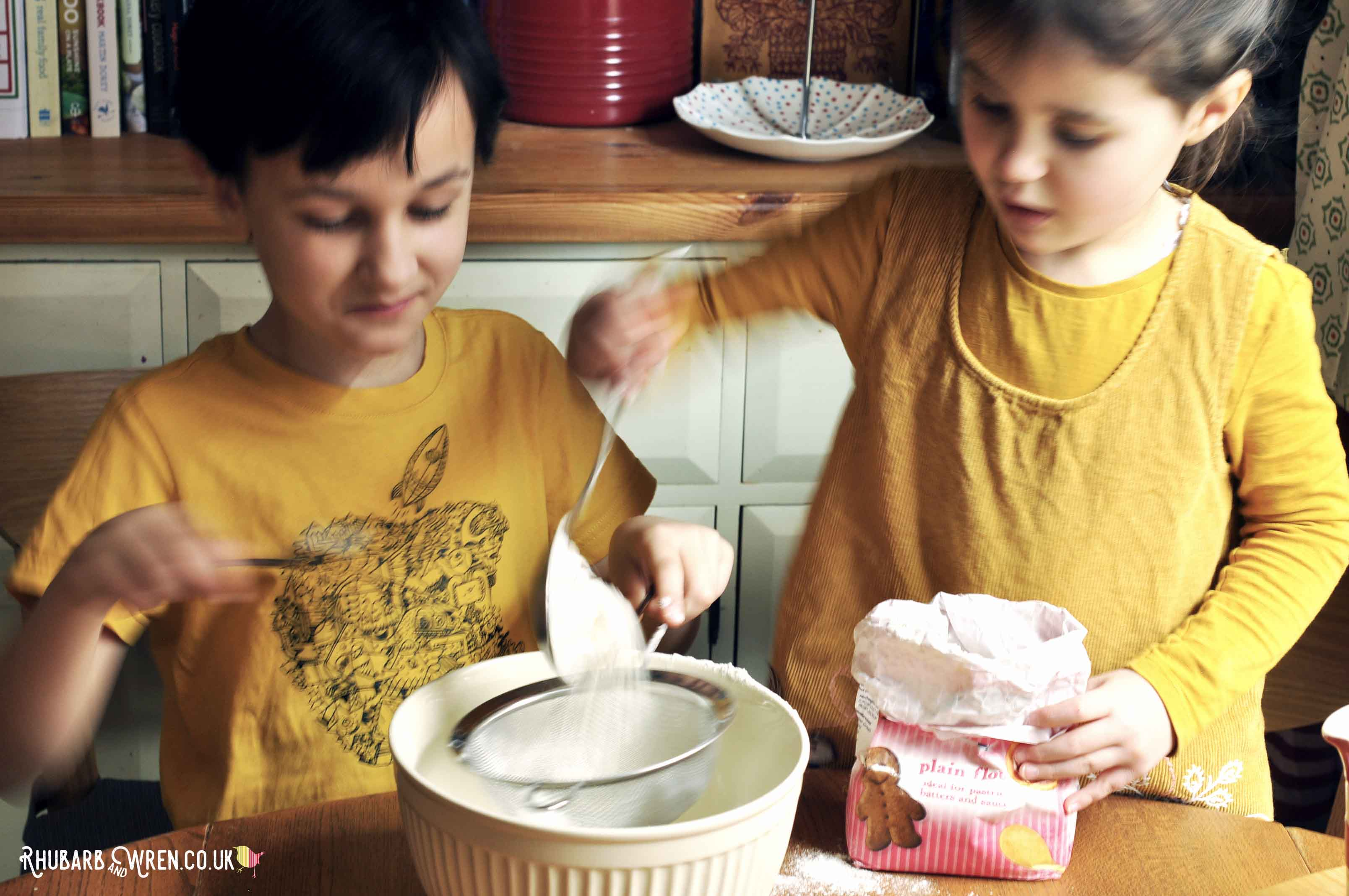 Kids mixing up pancake batter together.