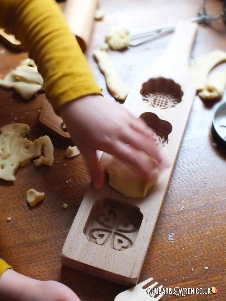Pressing play dough into aChinese wooden mooncake mould
