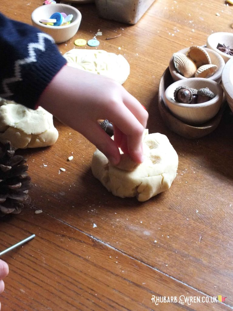 Stamping in play dough using acorns.