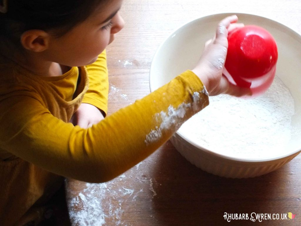 Child pouring flour from measuring cup into mixing bowl