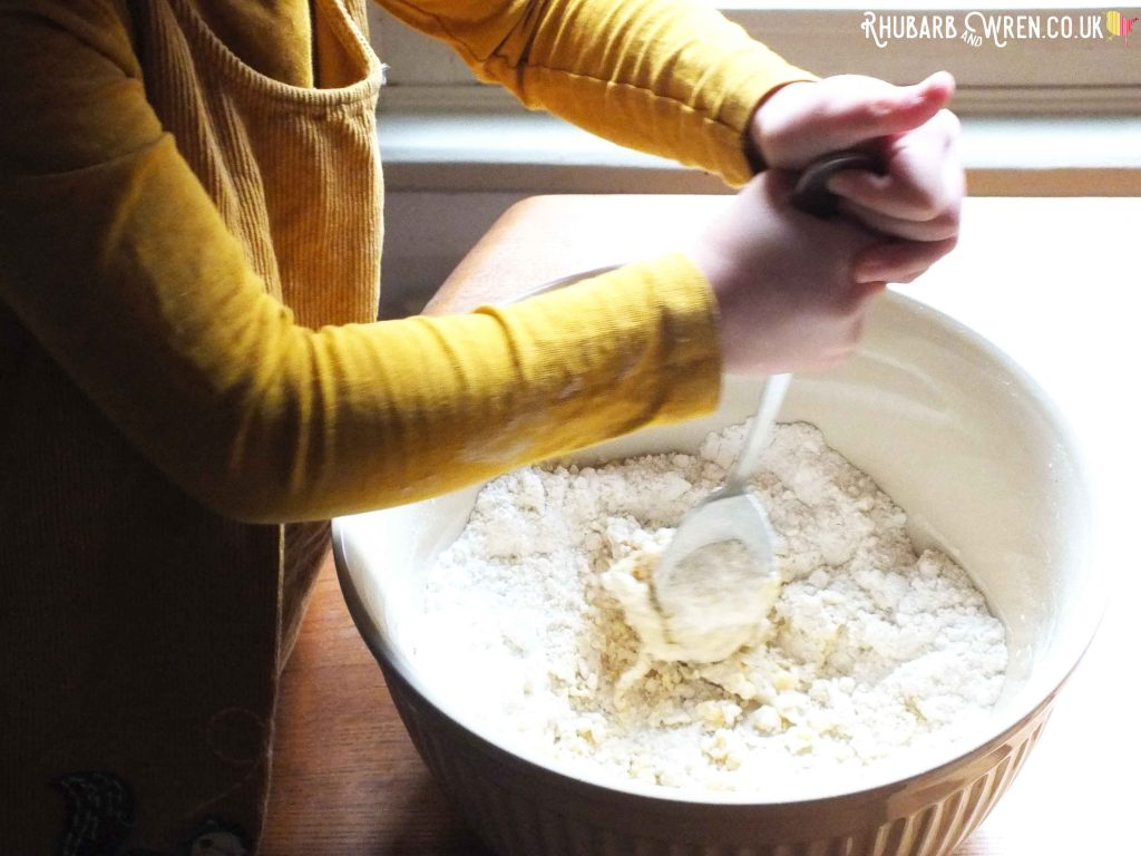 Child mixing dough in bowl with spoon