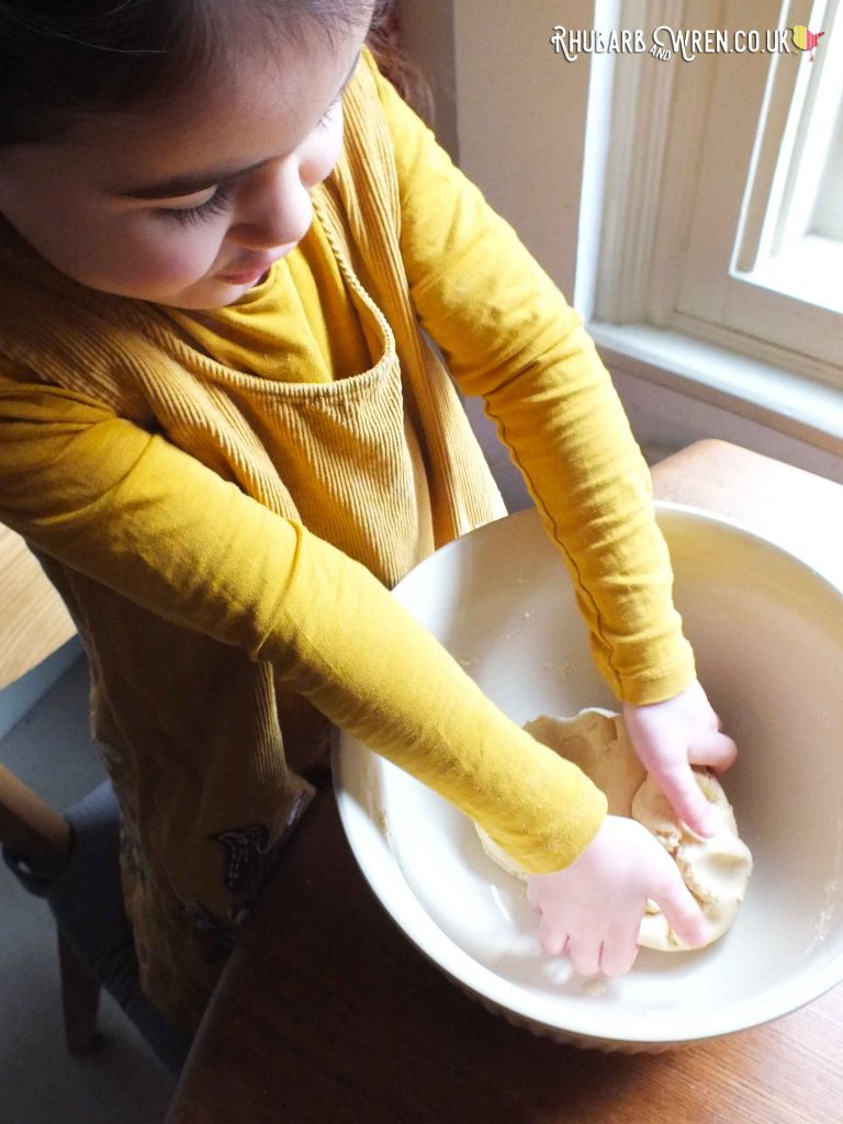 Child kneading dough in mixing bowl