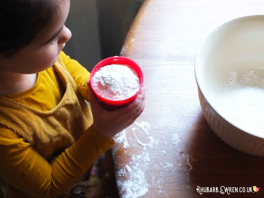 Child holding measuring cup full of flour