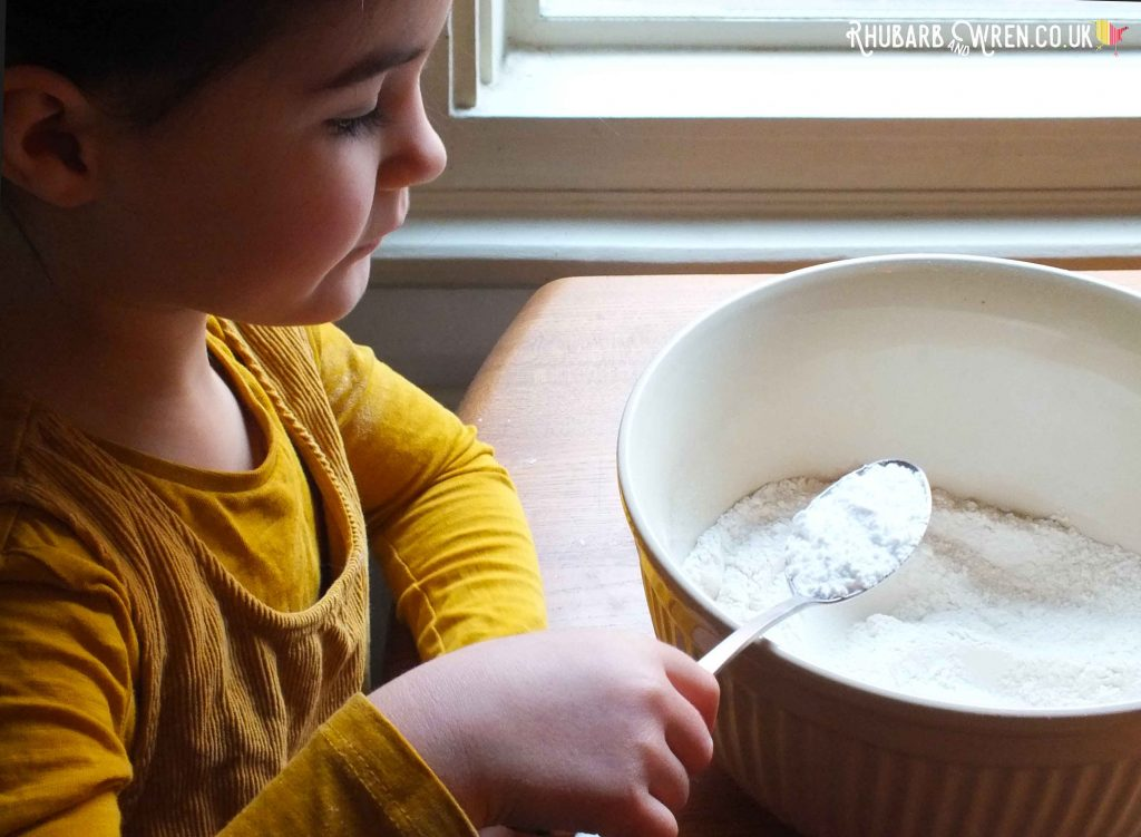 Child measuring flour with spoon over mixing bowl