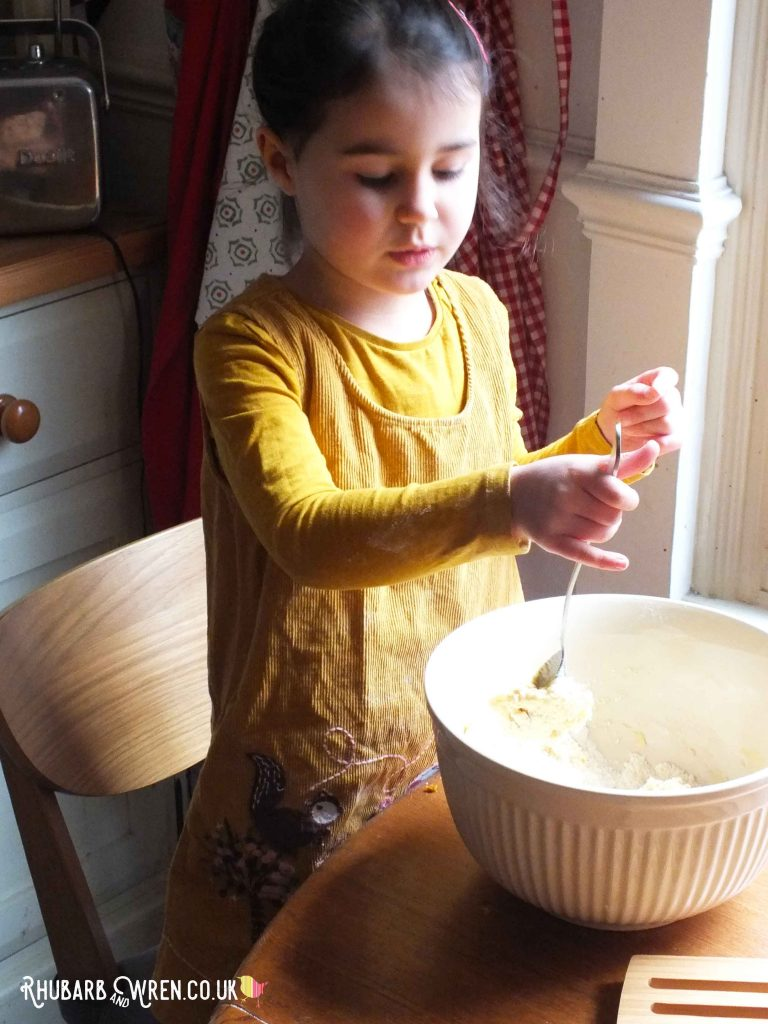 Child using spoon and mixing bowl
