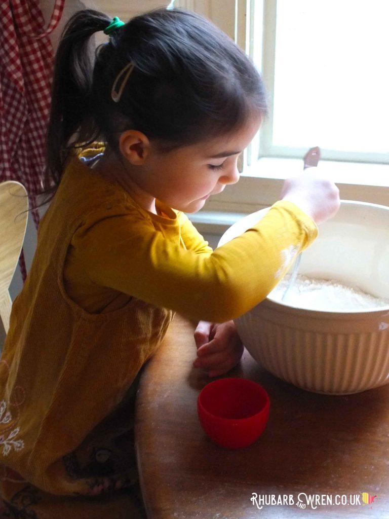 Child stirring flour in mixing bowl