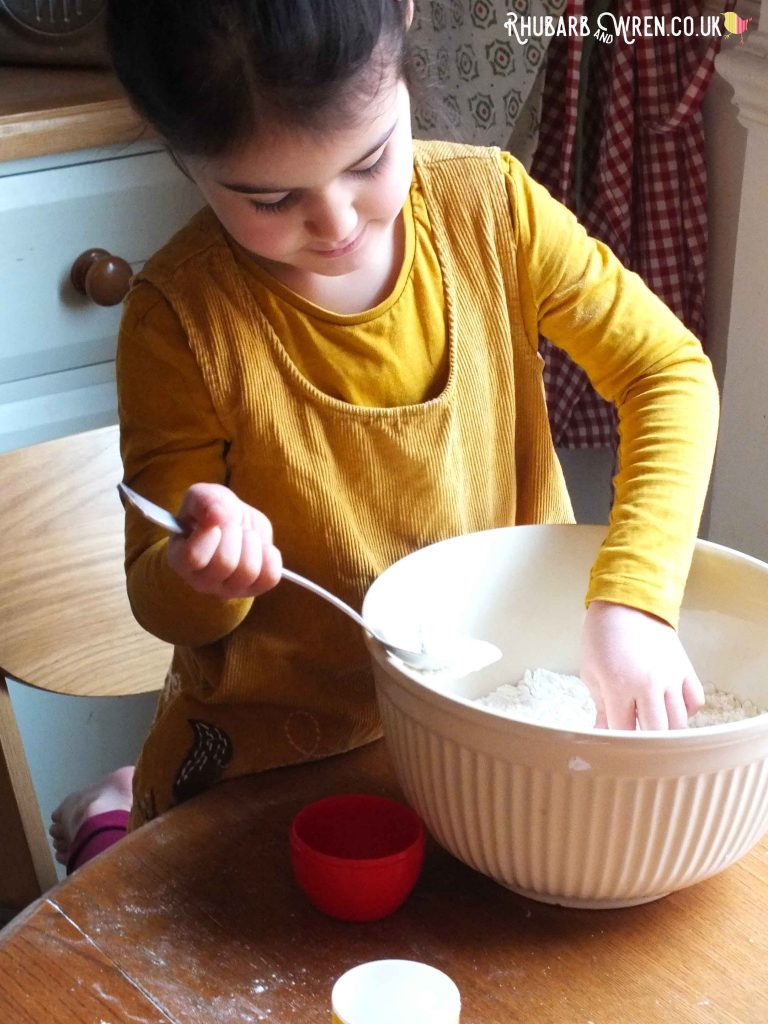 Child mixing flour by hand in bowl
