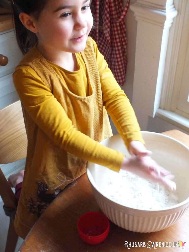 Child rubbing sticky flour hands over mixing bowl