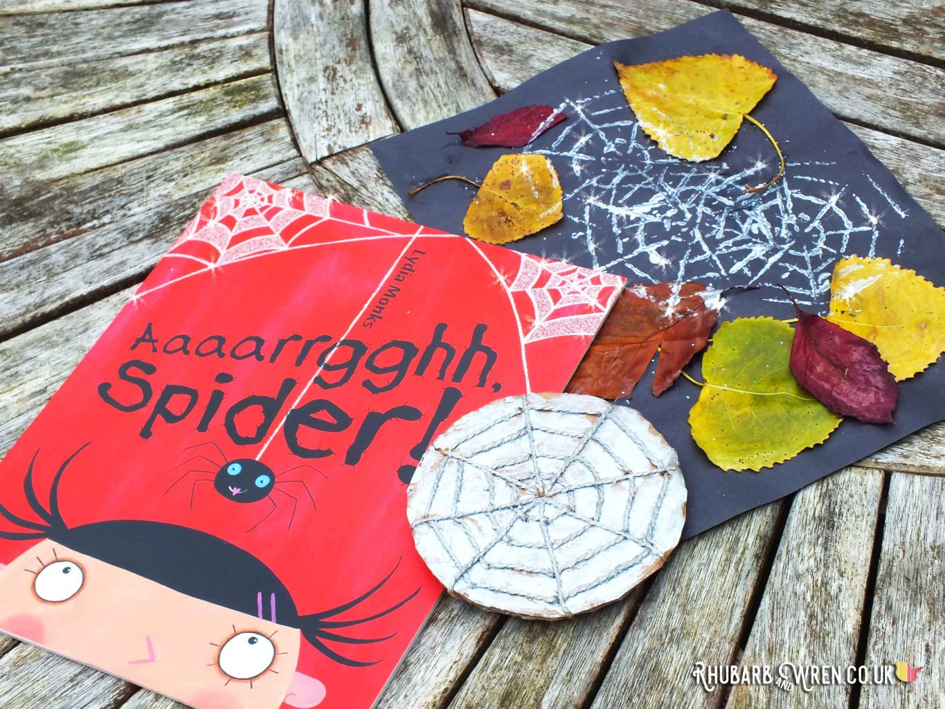 Book - Aaaarrgghh, Spider! lying on paper stamped with silver spiderwebs, plus cardboard spiderweb stamper.