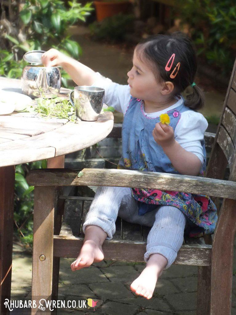 child making pretend tea in the garden