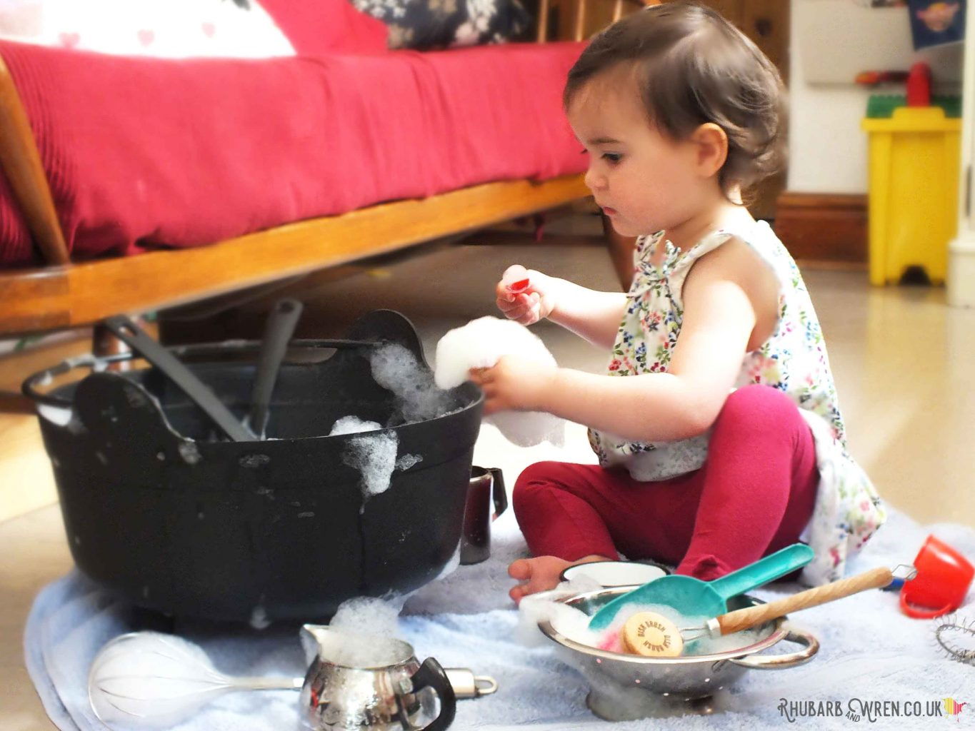 toddler playing with bubbles in plastic cauldron