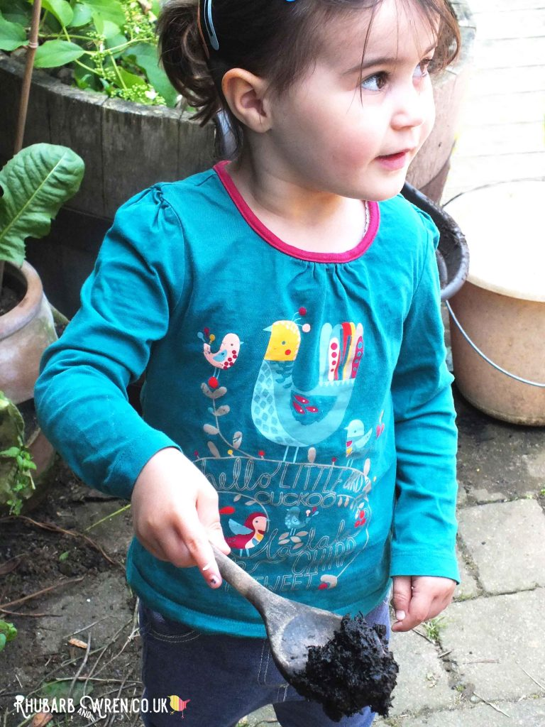 girl carrying spoon full of mud in mud kitchen