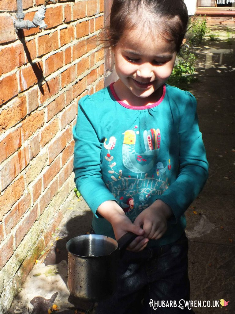 Smiling girl holding saucepan full of water for a mud kitchen