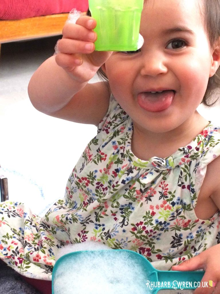 toddler playing with bubbles in toy cup
