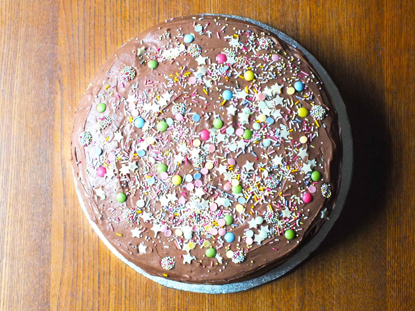 Looking down on chocolate cake covered in colourful sprinkles
