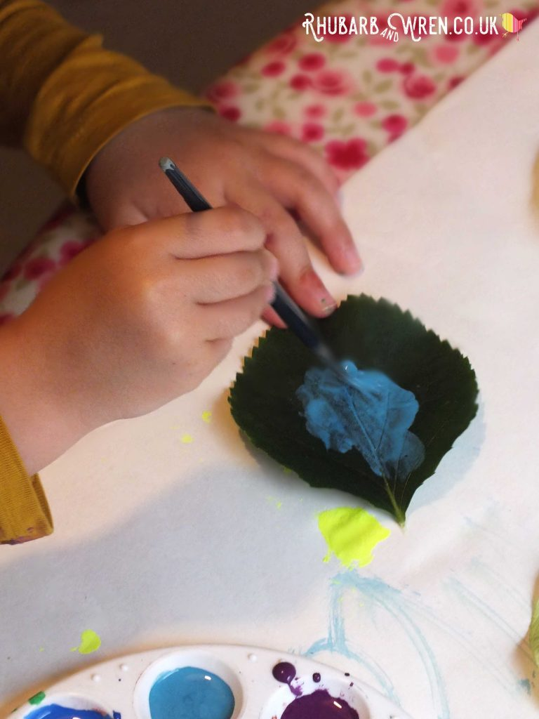 Child's hands holding paintbrush and painting leaf