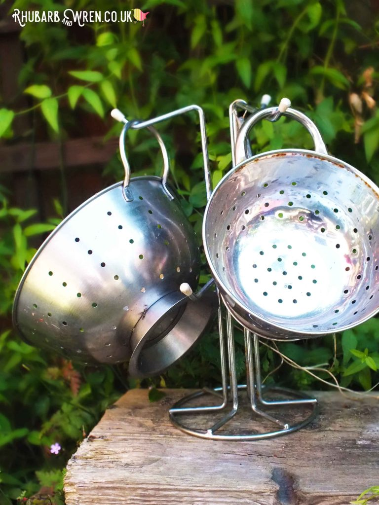 Two stainless steel colanders hanging on a cup stand in a mud kitchen