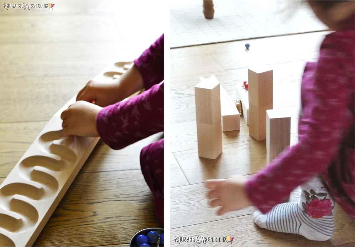 child playing with HABA wooden marble run blocks and winding track