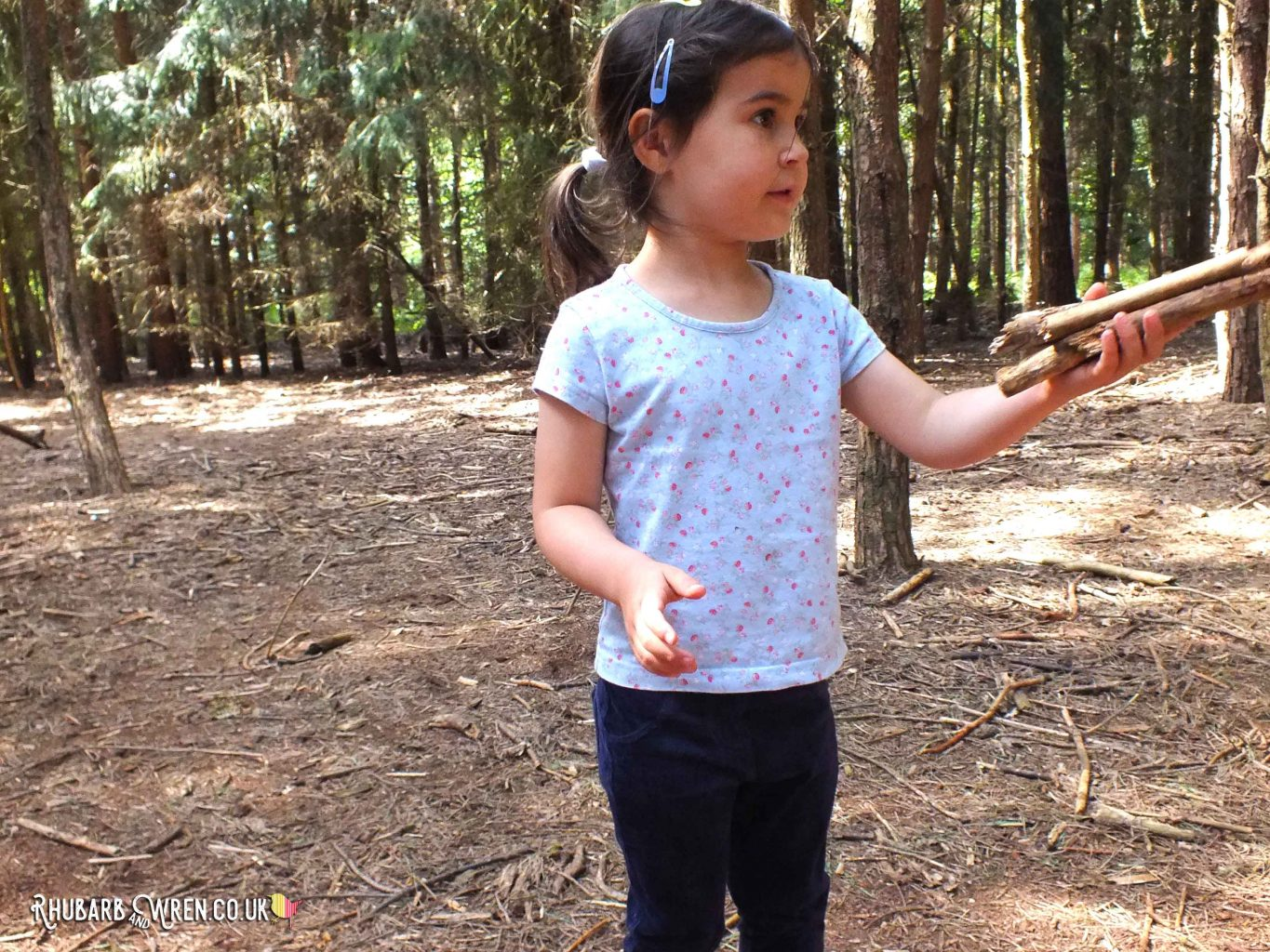 Girl picking up sticks in forest