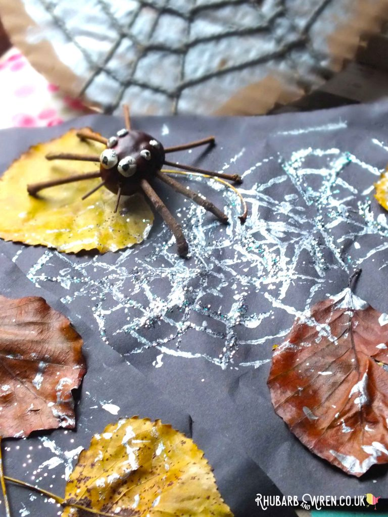 Printed silver spiderweb picture with a spider made from a conker and sticks sat on top.