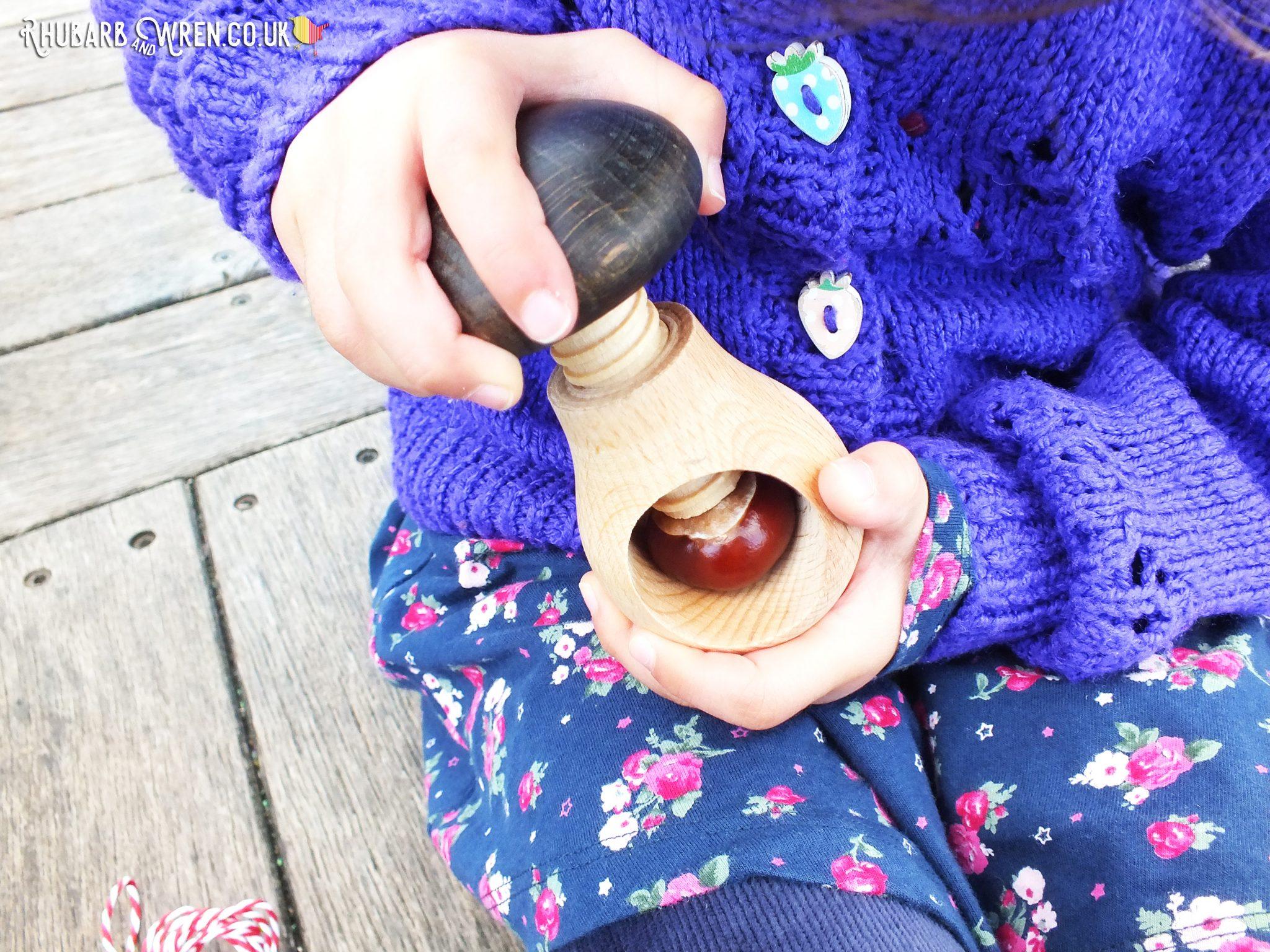 Girl holding conker held in nutcracker ready for drilling