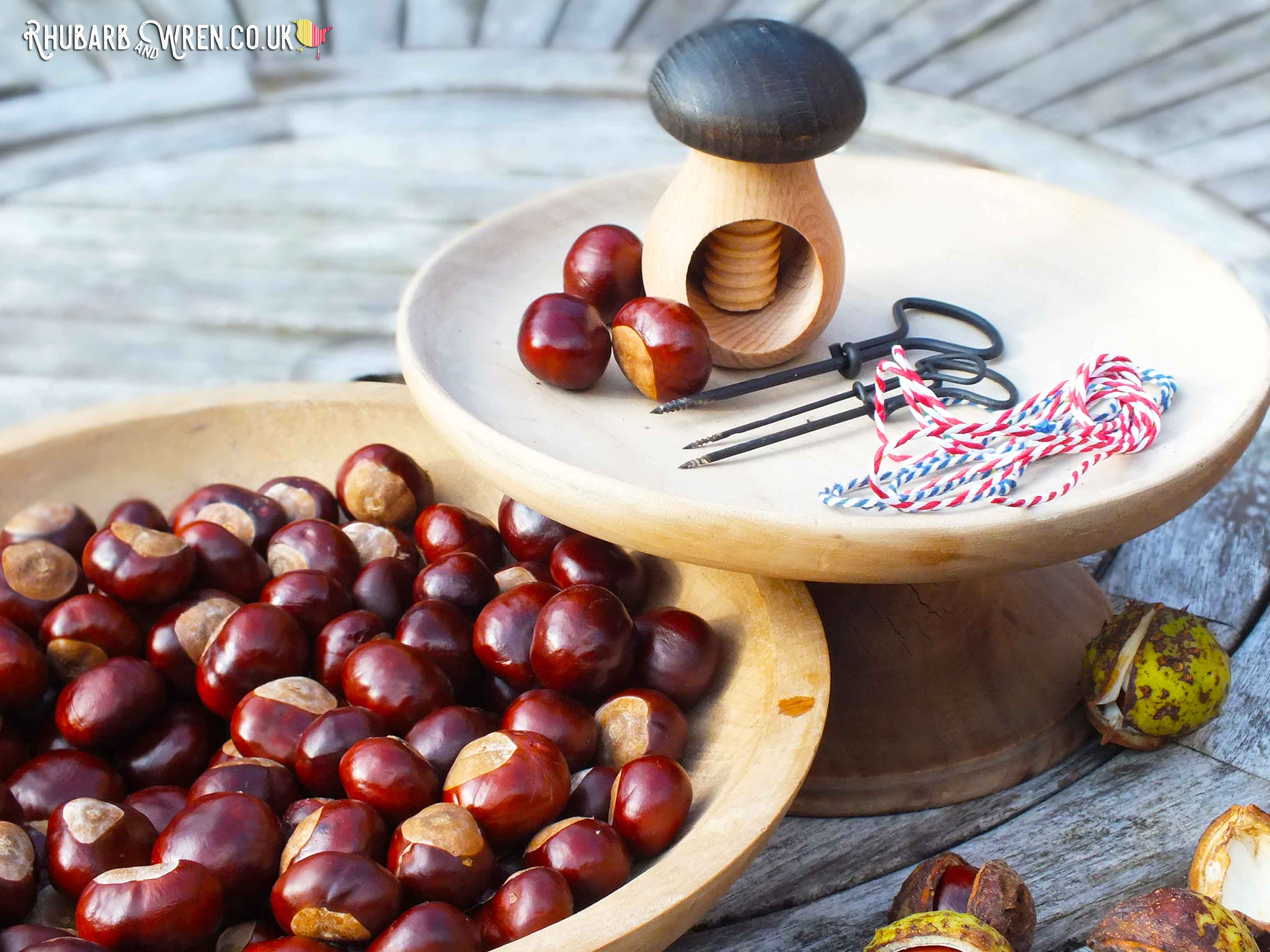 bowl of conkers with hand drill, string and nutcracker.