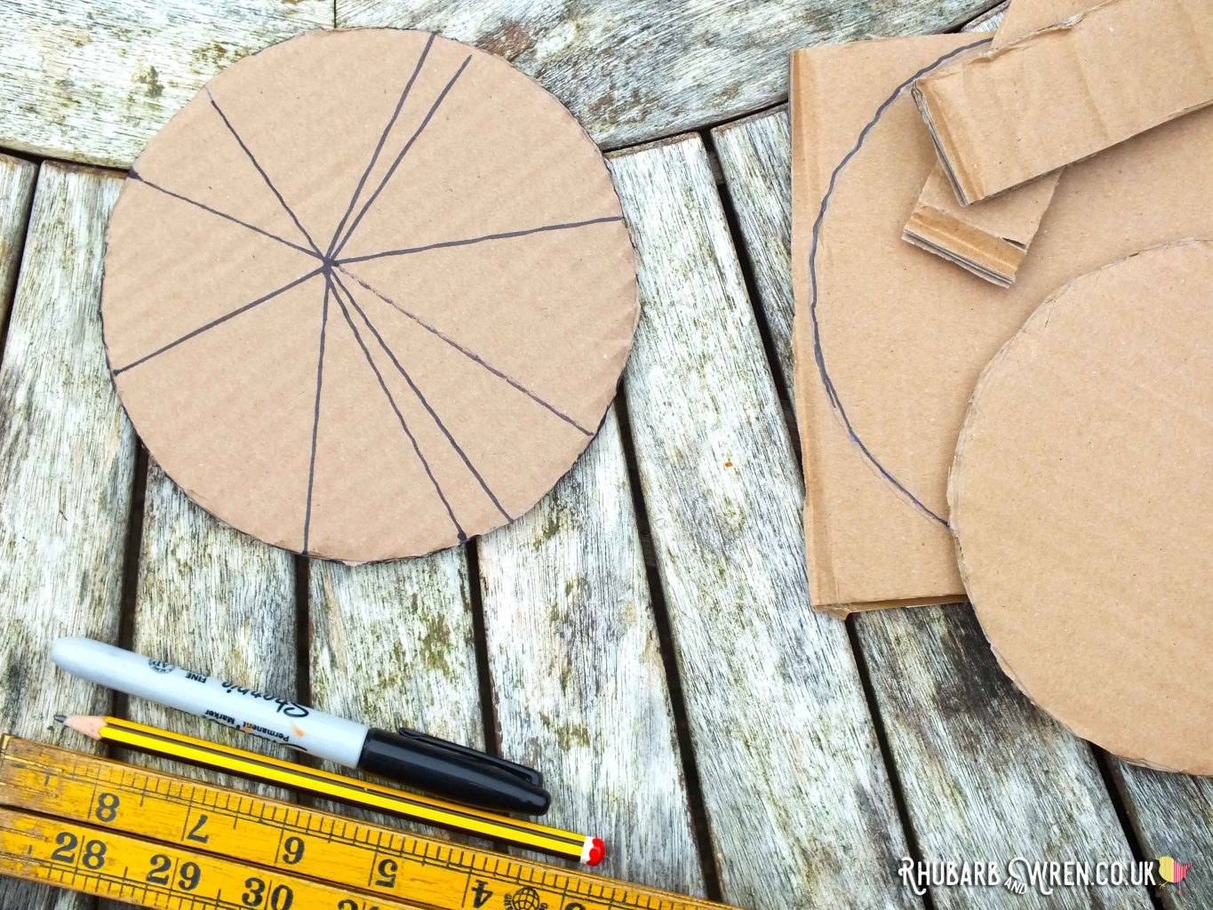 Drawing a spiderweb on a circle of corrugated cardboard